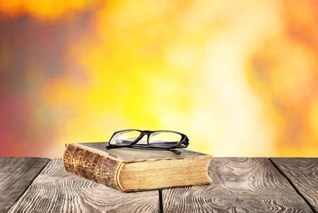 Old book with glasses on wooden table with orange background