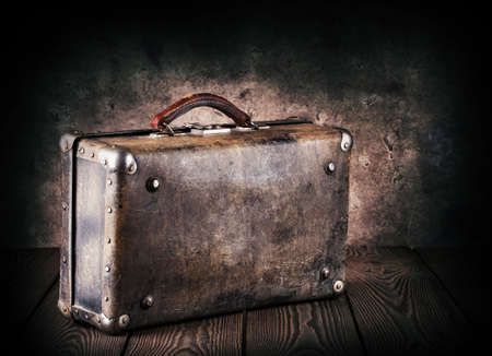 Old leather suitcase on a wooden table with dark background