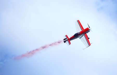 Rood en wit vliegtuigen die gekleurde rook in de hemel uitzenden. Het concept beweging en vrijheid.