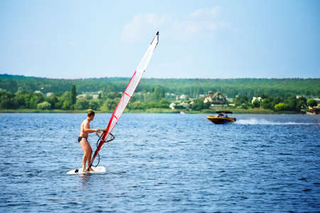 windsurf: Windsurfer on board with a white sail floating away