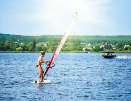 Windsurfer on the board with a white sail floating away