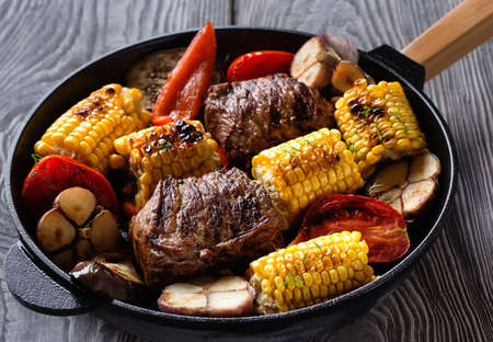 Fried meat and vegetables on a cast-iron frying pan