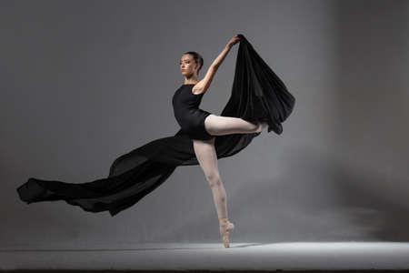 ballerina tights: Graceful ballerina in black tights posing with black cloth Stock Photo