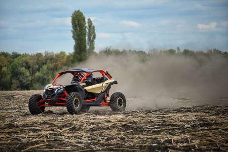Quad rijdt over een schuin veld Stockfoto