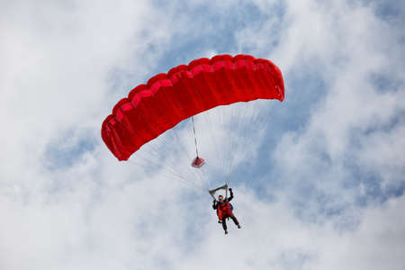 Parachuter descending with a red parachute