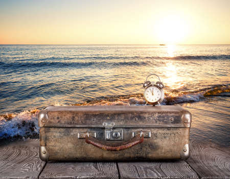 Old suitcase with clock on wooden planks against the sea