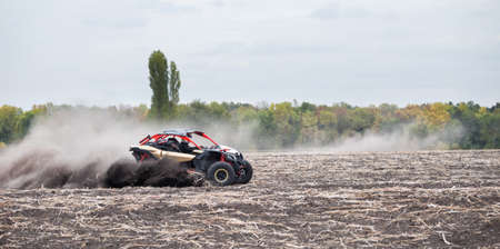 Quad bike quickly rides in dust clubs over plowed field Stock Photo - 94368224