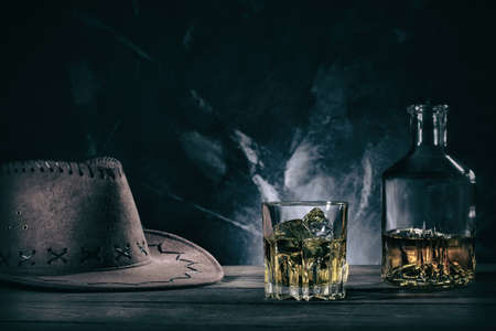 Glass of whiske and decanter with cowboy hat