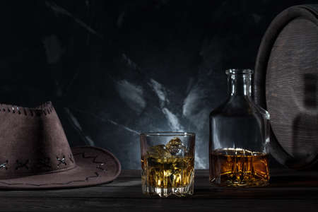 Transparent glass with whiskey cowboy hat and decanter