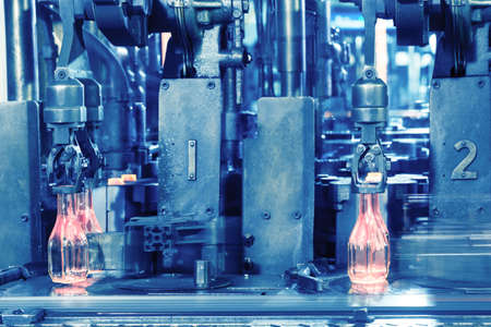 The hot glass bottles on conveyor are made by the glass manufact