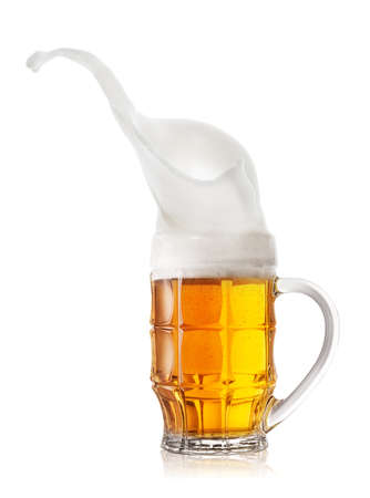 High splash of froth in a mug of beer. Isolated on white background.
