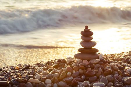 Pyramid of sea stones on the beach Imagens