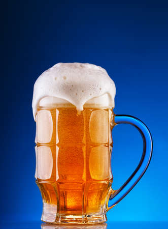 Faceted mug of the light beer with foam on blue background