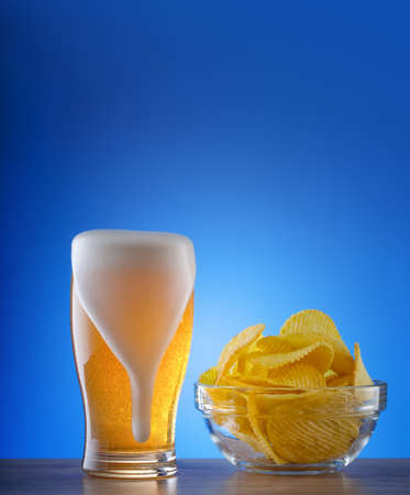 Glass of light beer with foam smudges and wavy chips Reklamní fotografie