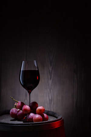 Glass of red wine and pink grapes on wooden barrel