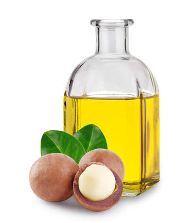 Macadamia oil in glass bottle and nuts with leaves