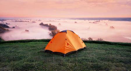 Orange tent on hill above misty river