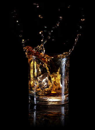 Splash of whiskey from an ice cube in glass