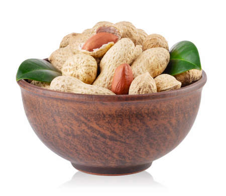 Peanuts with green leaves in clay plate