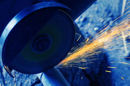 Sawing metal pipe with an electric saw. Sparks fly. Toning in blue 版權商用圖片