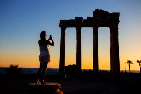 Silhouette of a girl photographing on the phone the Temple of Apollo at sunset. Side, Turkey