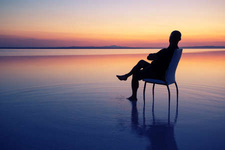 Silhouette of a man sitting on a chair in the middle of the lake at sunset. Calm water, dramatic sunset. concept of privacy, freedom and recreation