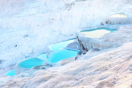 Natural Pamukkale travertine terraces filled with blue water