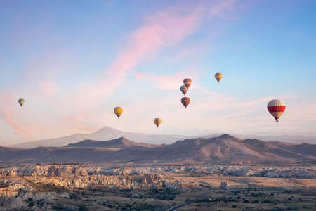 Ignition and take-off of balloons over the Valley of Love for Cappadocia. Early morning. Goreme, Turkey. Trade marks removed