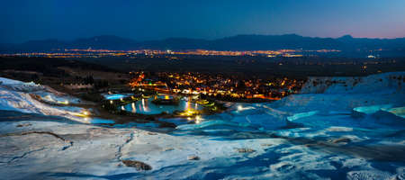 Travertine terraces and the city of Pamukkale lit by lights at night Stock Photo