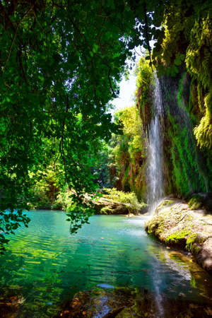 Kursunlu Nature Park and waterfall with lake. Bright greenery, turquoise lake water. Summer landscape. Antalya, Turkey 免版税图像