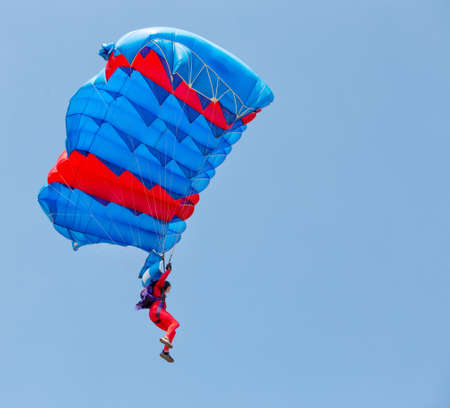Paratrooper in red suit descends under canopy of parachute in the blue sky.