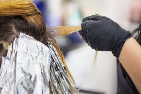 Hand of a hairdresser in black glove holds a lock of hair
