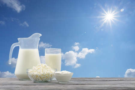 Dairy products in a glass bowl against a blue sky. Wooden table 스톡 콘텐츠