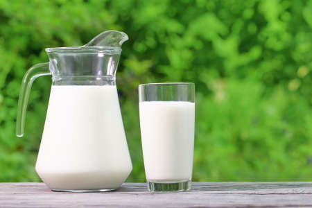 Jug and glass of milk on a wooden table. Natural green background. Natural Eco-Friendly Product Concept