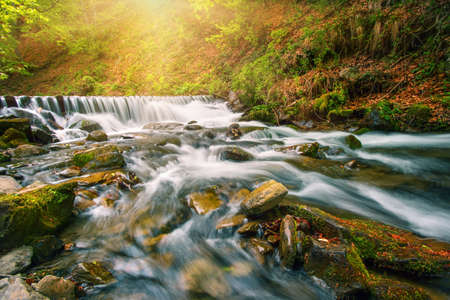 Waterfall on a mountain river in the autumn forest under bright sun
