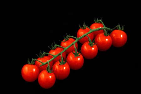 黒の背景に赤いトマトの束