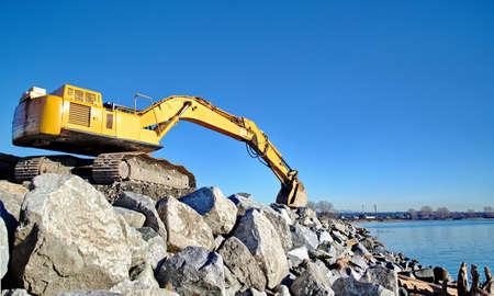 sand quarry: Excavator on large rocks on the beach
