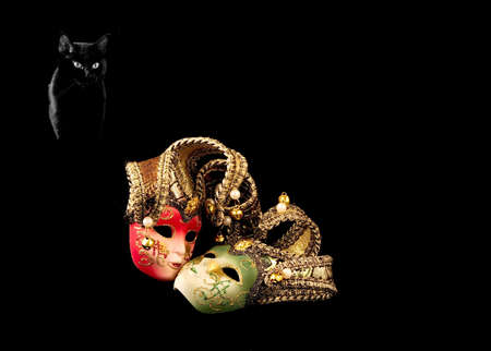 period costume: Two carnival mask and a black cat on a black background Stock Photo