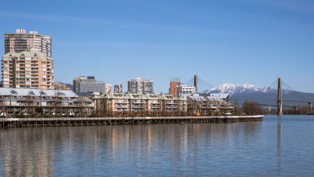 fraser river: Apartment Buildings on the waterfront of New Westminster Downtown. Fraser River, Bridge and mountain view.
