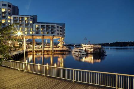 Hotel near the river evening illumination, paddle wheeler and restaurant