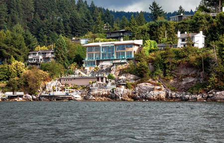 district of columbia: A village on a rocky beach in the  Strait of Georgia in West Vancouver  British Columbia, a coastline and a forest.