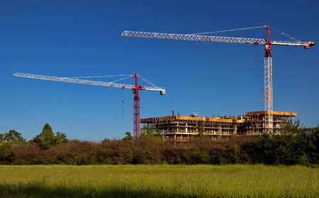working stiff: Construction site in the green zone. Two construction cranes provide the construction of a high-riser Stock Photo
