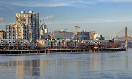 Residential District on the waterfront of New Westminster Downtown. Fraser River, Bridge and mountain view and new construction in the city. Stock Photo