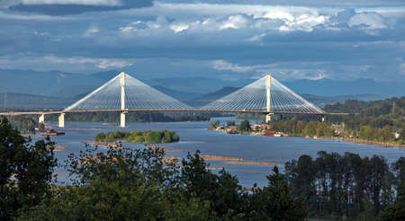 Panoramic view of the Fraser River and Port Mann Bridge against the backdrop of the the mountain ridge.  A railroad track over the Fraser River on The Trans Canada Hgw between Coquitlam and Surrey British Columbia