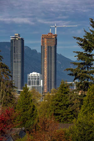 New construction of high-rise buildings in   Burnaby City, construction site in the center of the city against the backdrop of a mountain ridge Vancouver - Canada.