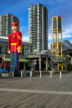 This tin soldier is 32 feet tall and 5 tons in weight on the Quay in New Westminster, British Columbia, Canada and stands on the banks of the Fraser River. Against the backdrop of the skyscrapers of the new residential area of the city of New Westminster