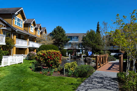 Residential District in Richmond City, a village of townhouses with pond and fountain, blossom of sakura, green grass bushes and trees in the territory of residential complex, Vanсouver, British Columbia