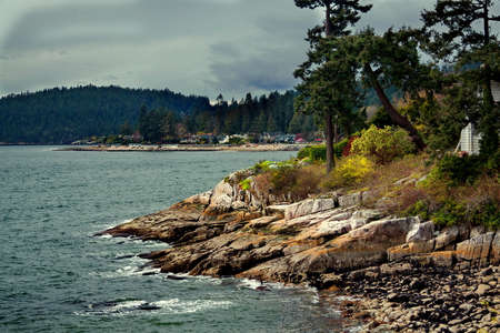 Rocky beach in the Strait of Georgia, British Columbia, the coastline and the coastal village on the opposite shore of the bay, forests against the backdrop of mountain landscapes