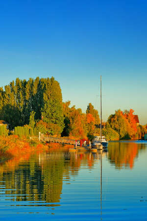 Autumn time, Marina near the riverbank overgrown with yellowed trees, parking for two yacht against the blue sky Stok Fotoğraf