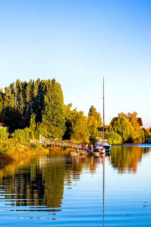 Autumn time, Marina near the riverbank overgrown with yellowed trees, parking for two yacht against the blue sky